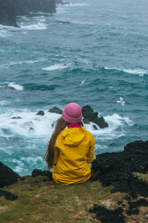 rear view of woman in yellow raincoat sitting on cliff in front of stormy ocean, iceland