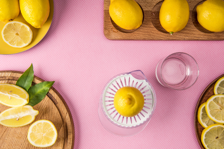 top view of yellow lemons and juice squeezer on pink background