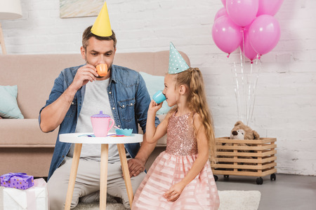 father and daughter playing tea party at home with pink balloons