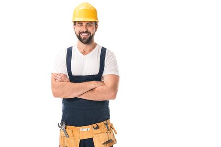 hübscher glücklicher Arbeiter im Schutzhelm und im Werkzeuggürtel, die mit verschränkten Armen stehen und an der Kamera lokalisiert auf Weiß lächeln