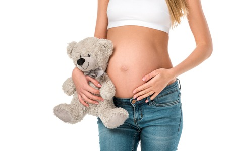 cropped view of pregnant woman holding teddy bear isolated on white Foto de archivo - 109837809