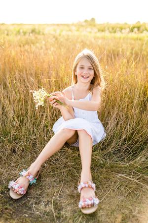 happy little child in white dress with field flowers bouquet sitting in field