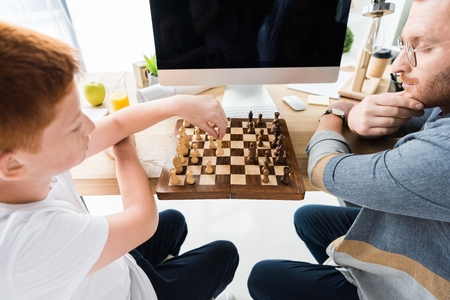 father and son playing chess at table with computer at home
