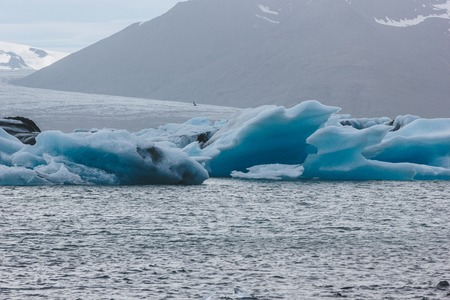 glacier ice pieces floating in lake in Iceland with mountain silhouette on background