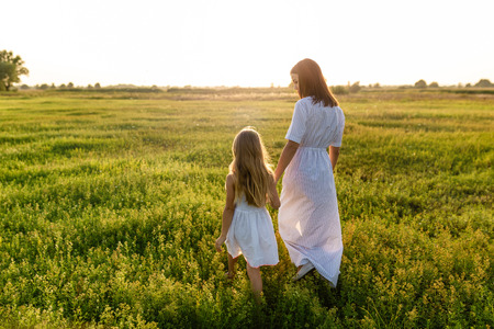 mother and daughter holding hands and walking by green meadow with sunset sky on background