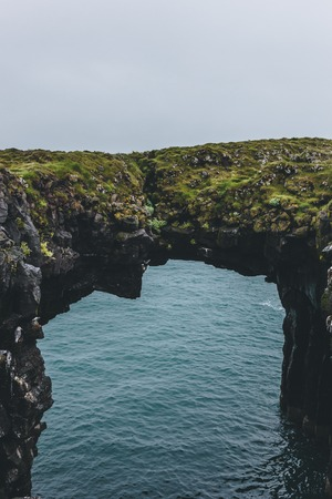 mossy cliff in shape of arch with blue ocean on background in Arnarstapi, Iceland Stock Photo