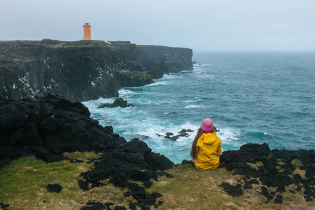 rear view of woman in yellow raincoat sitting on cliff in front of ocean and looking at lighthouse, Iceland Stockfoto