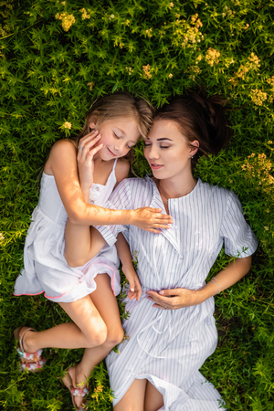 overhead view of relaxed mother and daughter lying on flowery meadow Banque d'images - 109838092