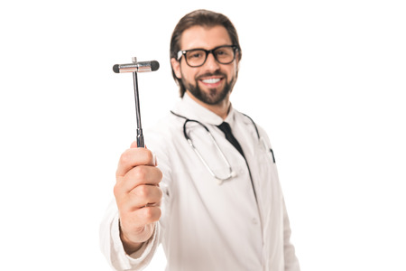 close-up view of happy doctor holding reflex hammer and smiling at camera isolated on white