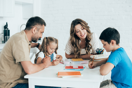 parents helping children with homework at table at home Banque d'images