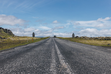 road with car in highlands under blue cloudy sky in Iceland
