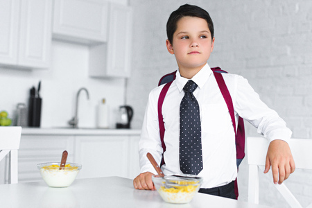 portrait of pensive boy in school uniform with backpack standing at table with breakfast in kitchen, back to school concept