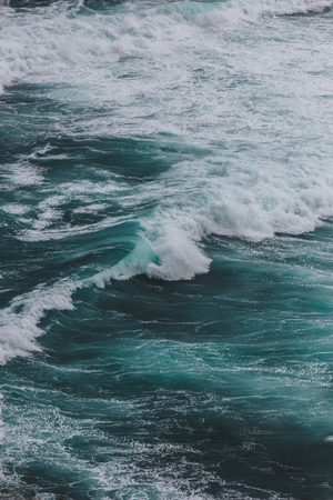 dramatic shot of blue ocean with foamy waves for background