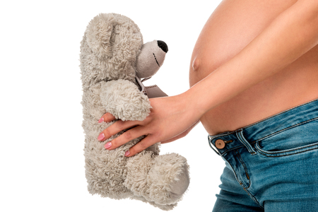 partial view of pregnant girl holding teddy bear in front of belly isolated on white Foto de archivo - 109842727