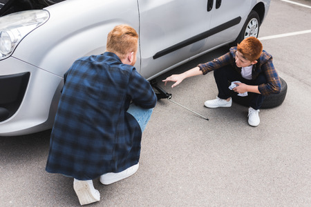 father lifting car with floor jack for changing tire, son pointing on something Stok Fotoğraf