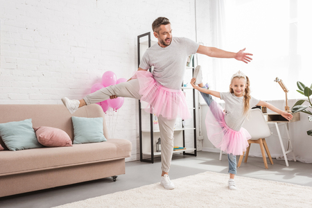 front view of father and daughter in tutu skirts standing on one leg Foto de archivo - 109845684