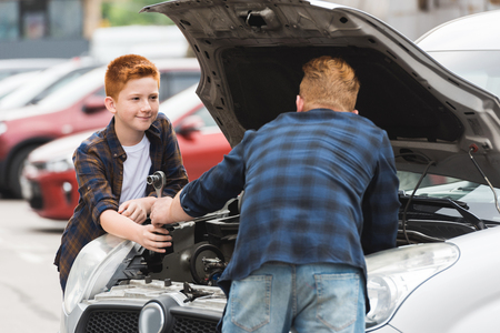 son giving tool for repairing car to father Stock Photo