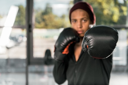 selective focus of african american male boxer in boxing gloves exercising at gym