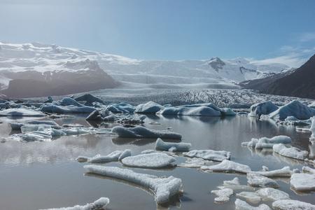 melting glacier ice floating in lake in Fjallsarlon, Iceland under blue sky