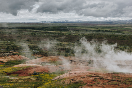 aerial view landscape with volcanic vents under cloudy sky in Haukadalur valley in Iceland Stock Photo