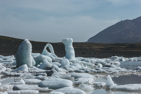 melting glacier ice pieces on lake shore in Fjallsarlon, Iceland
