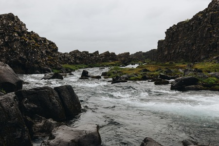 beautiful mountain river flowing through highlands under cloudy sky in Thingvellir national park in Iceland