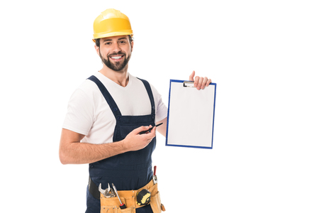 happy construction worker in hard hat and tool belt holding blank clipboard and smiling at camera isolated on white Stock fotó
