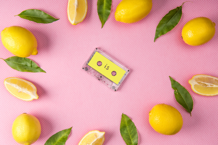 top view of frame made from yellow lemons and leaves with vintage audio cassette inside on pink Stock Photo