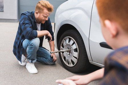 father changing tire in car with wheel wrench, son sitting near Stok Fotoğraf