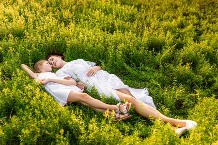 beautiful mother and daughter relaxing while lying in flowery meadow Banque d'images - 109848003