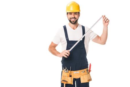 Guapo obrero feliz sosteniendo cinta métrica y sonriendo a la cámara aislada en blanco