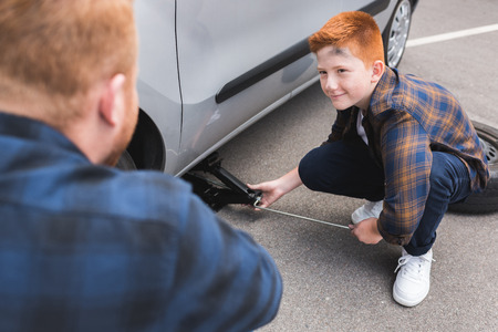 son lifting car with floor jack for changing tire and looking at father Stok Fotoğraf