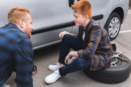 father and son changing tire in car with floor jack and looking at each other Stok Fotoğraf