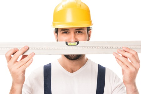 handsome construction worker in hard hat holding level tool and looking at camera isolated on white Banco de Imagens