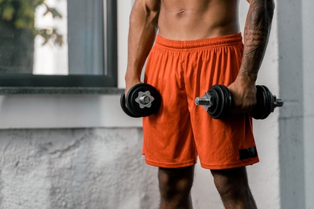 cropped image of tattooed african american sportsman exercising with dumbbells at gym