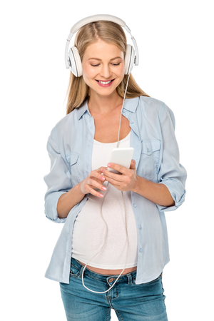 attractive pregnant woman listening music with headphones and smartphone isolated on white Foto de archivo - 109856667