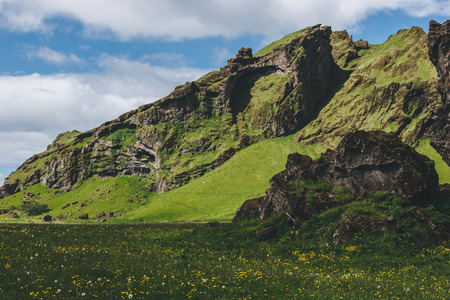 scenic view of green meadow near mountain under cloudy blue sky in Iceland Stock Photo