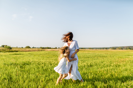 mother and daughter having fun together and embracing in green meadow on windy day