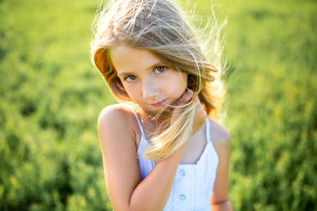 close-up portrait of cute little child in white dress posing in green field and looking at camera