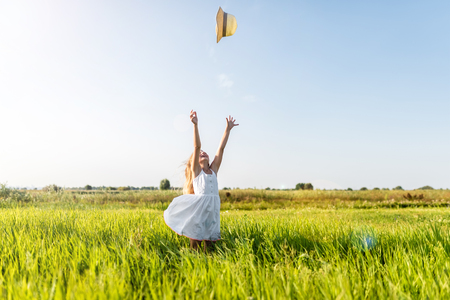 adorable little child in white dress throwing hat on field Stock Photo