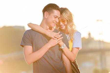 girlfriend hugging boyfriend on river beach in evening and they holding hands 版權商用圖片