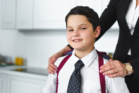 partial view of mother in suit and son in school uniform with backpack in kitchen at home, back to school concept Banco de Imagens