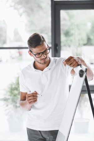 young focused businessman making presentation at white board in office