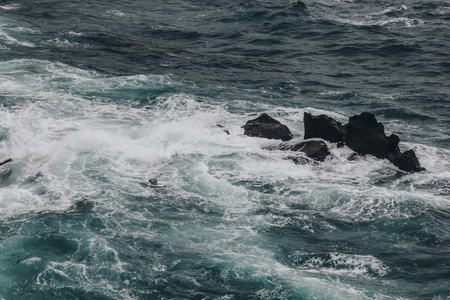 dramatic shot of blue ocean waves crashing on rocks for background 写真素材