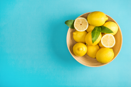 top view of fresh lemons with leaves in wooden plate on turquoise background Stok Fotoğraf