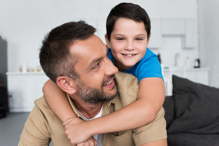 portrait of smiling boy hugging father and looking at camera at home 版權商用圖片