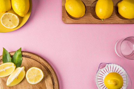 top view of juice squeezer and fresh lemons on wooden boards on pink background