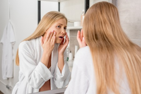 adult pregnant woman with skin problems looking at her face through mirror in bathroom Foto de archivo - 109886414