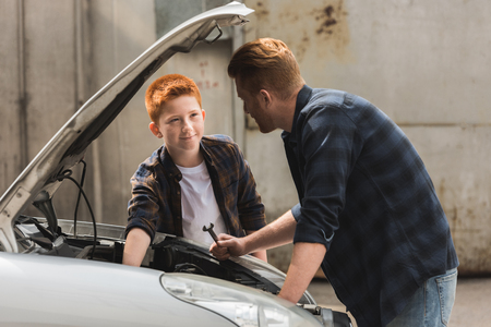 side view of ginger hair father and son repairing car with open hood