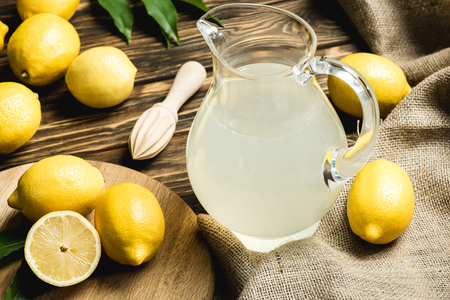 glass jug with fresh juice, squeezer and yellow lemons on sacking on wooden surface Stockfoto